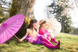 Two sisters with parasols sit beneath a tree in springtime, Burnaby B.C.