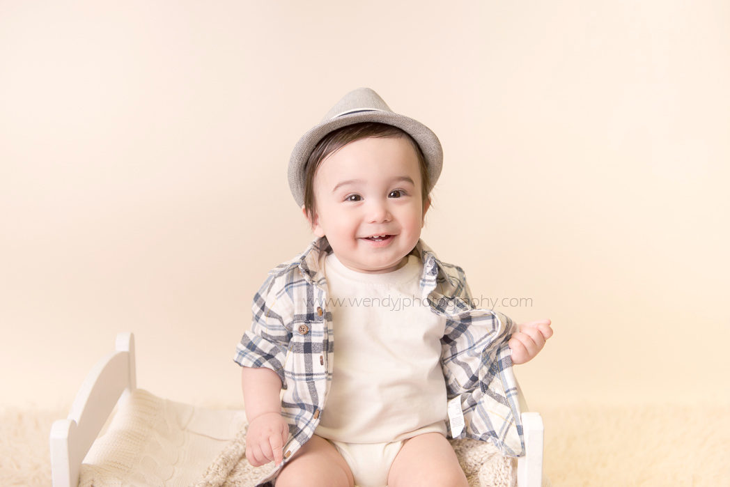 Smiling nine month old boy. Portrait by Vancouver baby photographer Wendy J Photography.