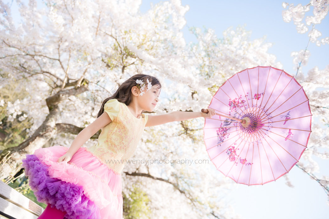 Young girl with pretty purple parasol stands beneath a blossom covered tree. Child photography in Vancouver B.C.