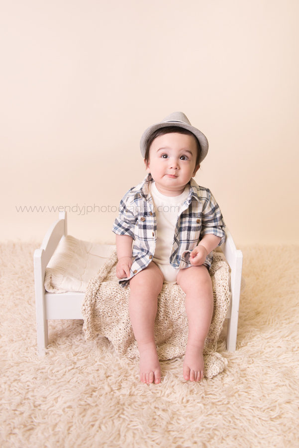 Cute baby boy sits on miniature bed during photo session.
