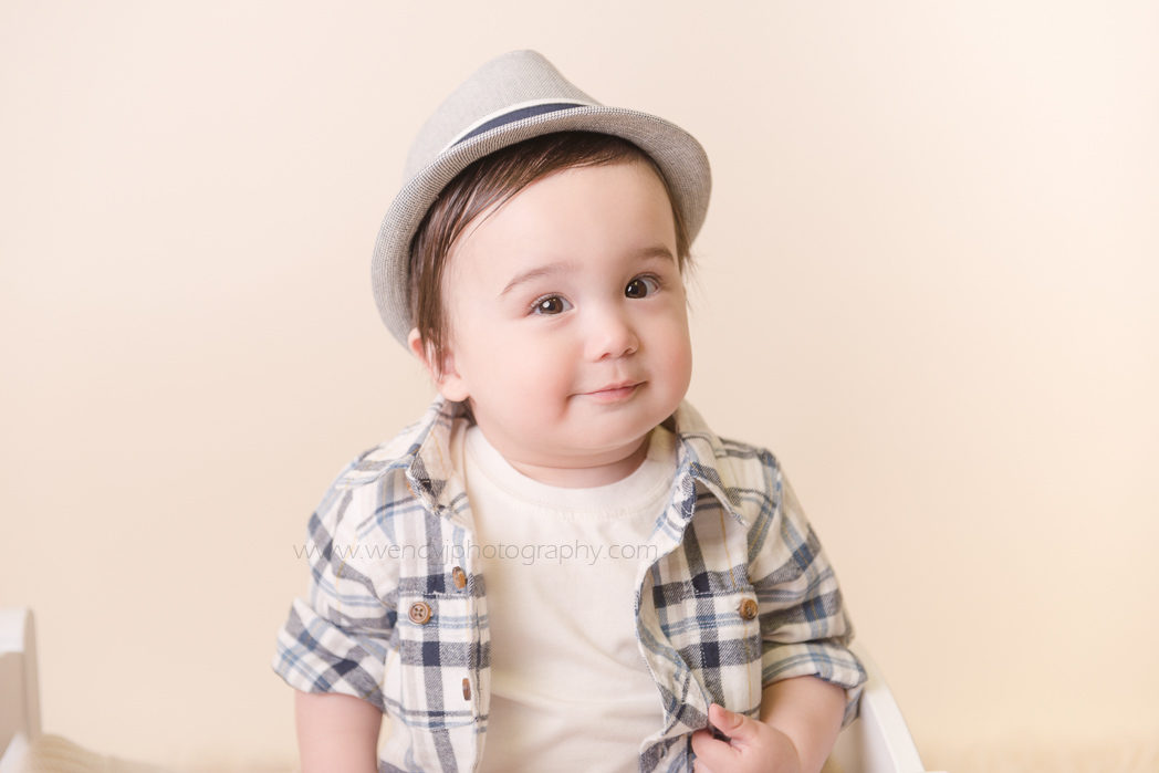Cute baby boy wearing a hat during a baby portrait session by Wendy J Photography.