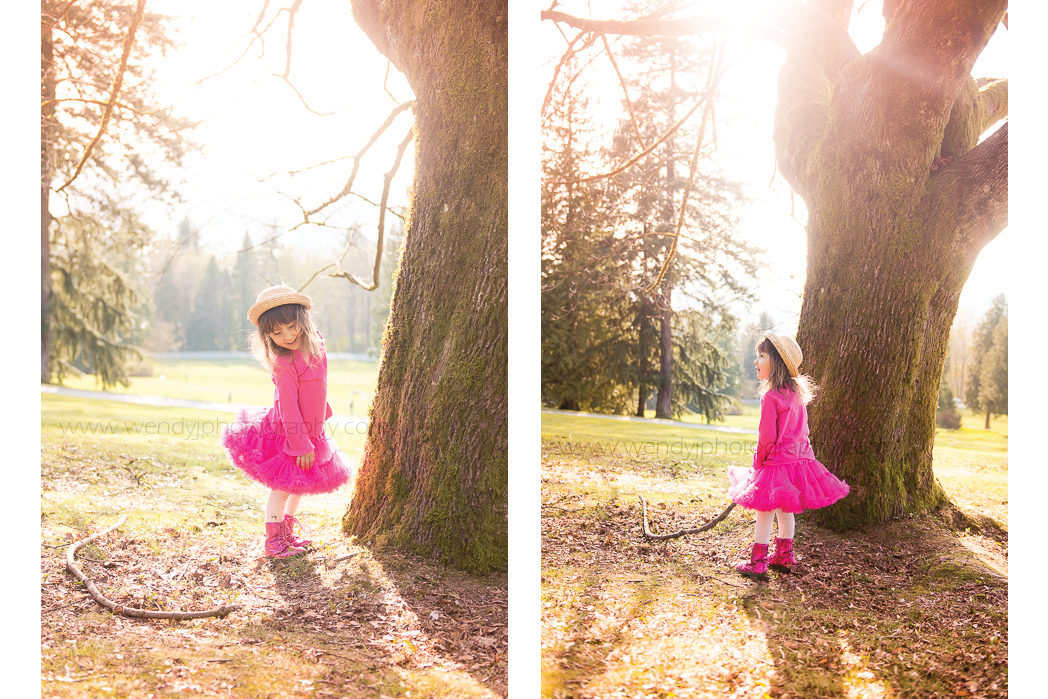 Young girl on a sunny day stands beside a large tree in a park.