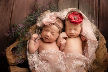 Twin girl newborns sleeping in wooden bowl.