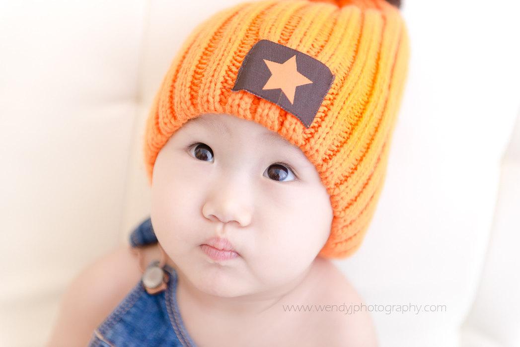 One year old girl wearing an orange beanie hat.