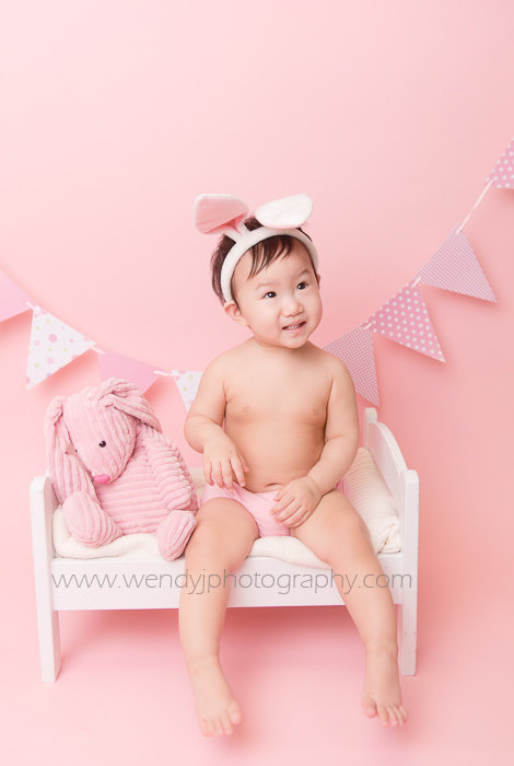 Cute 1 year old girl wearing bunny ears sitting on a miniature bed during a Burnaby, Vancouver B.C. child portrait photography session.