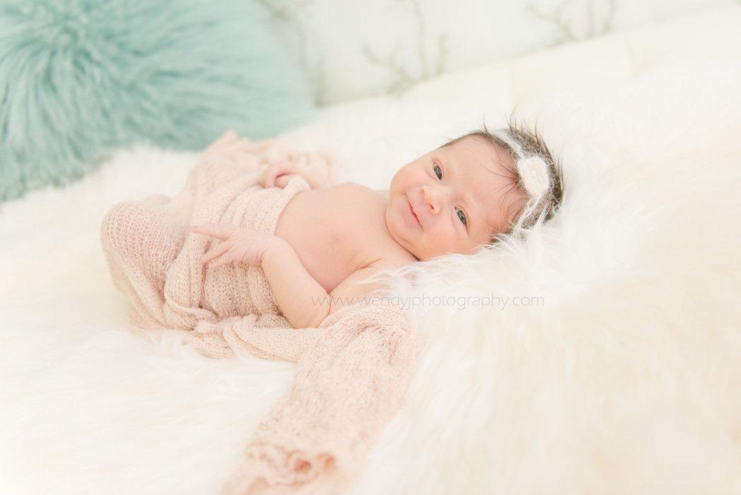 Smiling newborn baby girl.