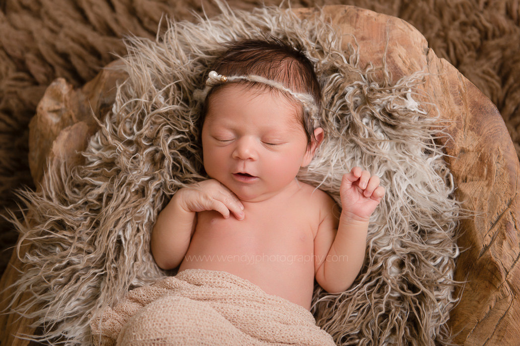 Newborn baby girl lying in a natural wooden bowl.